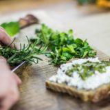 ruce krájející bylinky pro chléb s bylinkovým pestem obsahujícím zelené barvivo chlorofyl